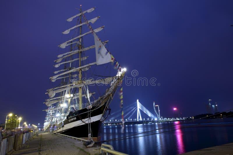 Verlichtte de lange schepen van schepenrassen in Riga stock foto's