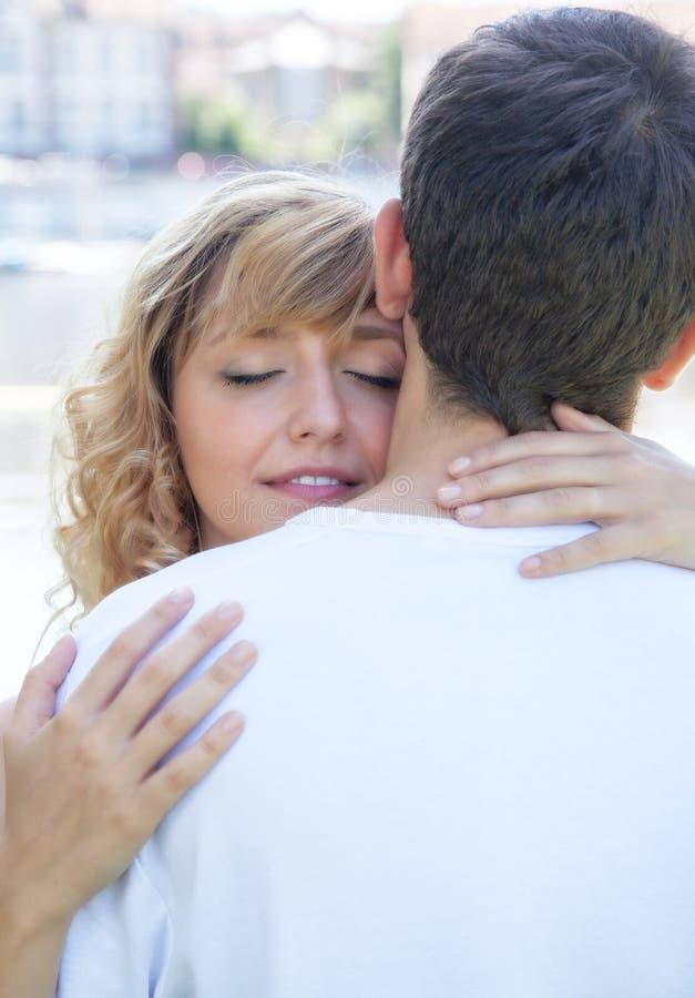 Verliebte Frau, die ihren Freund umfasst stockfotografie