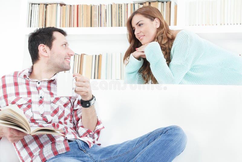 Verliebte Frau, die neugierig auf ihre Mannunterhaltung hört stockbild