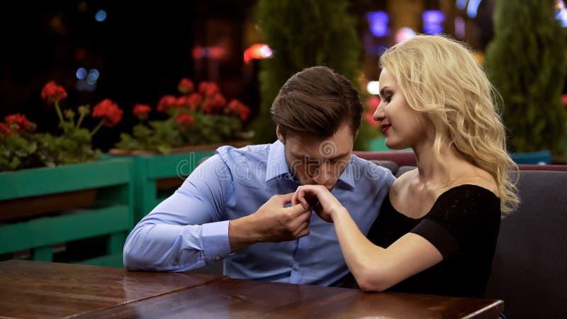 Verliefde bewonderaar het kussen hand die van zijn mooie dame, in comfortabel restaurant zitten royalty-vrije stock foto