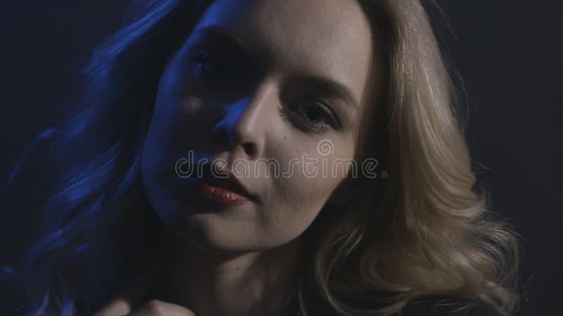 Verlieren Sie herauf Porträt des Schönheitsgesichtes mit dem gelockten langen blonden erstaunlichen Haar, das auf schwarzem Hinte stockbild