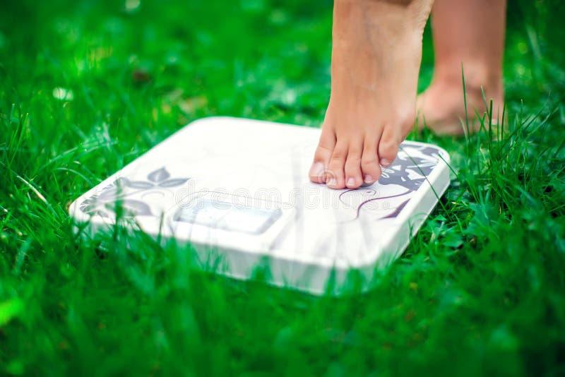 Verlies gewichtsconcept Een persoon op een schaal op een gras die ki meten stock afbeeldingen