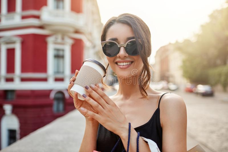 Verlies omhoog portret van jong mooi Kaukasisch meisje die met donker haar in zonnebril en zwarte kleding met tanden glimlachen royalty-vrije stock fotografie