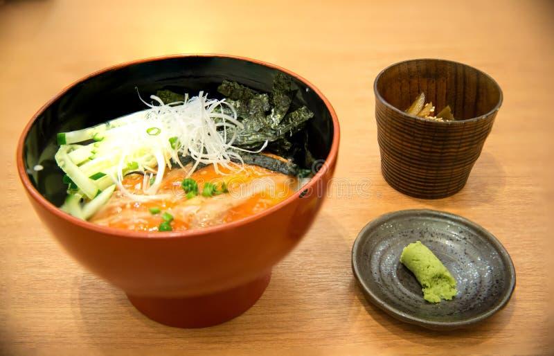 verlies omhoog vers die zalmvuller en ei op Japanse rijst in witte kom wordt bedekt stock foto