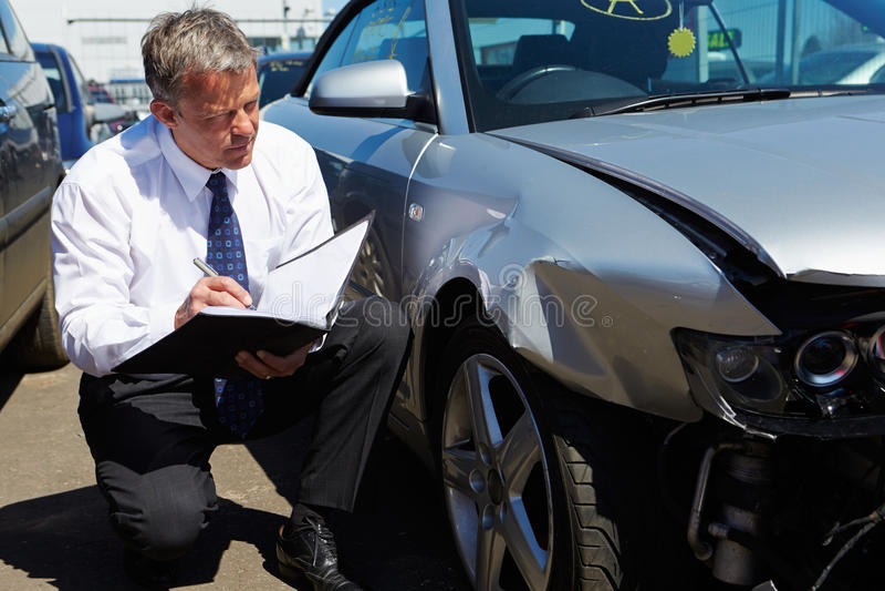 Verliesregelaar het Inspecteren Auto Betrokken bij Ongeval stock afbeelding