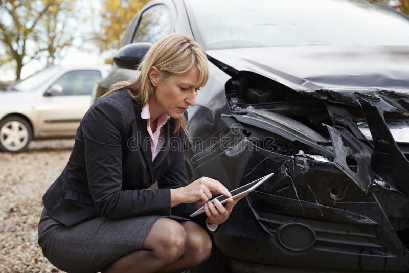Verliesregelaar met Digitale Tablet die Beschadigde Auto inspecteren royalty-vrije stock afbeelding