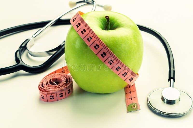 Verliezend gewicht - groene appel, die band en stethoscoop meten royalty-vrije stock afbeelding