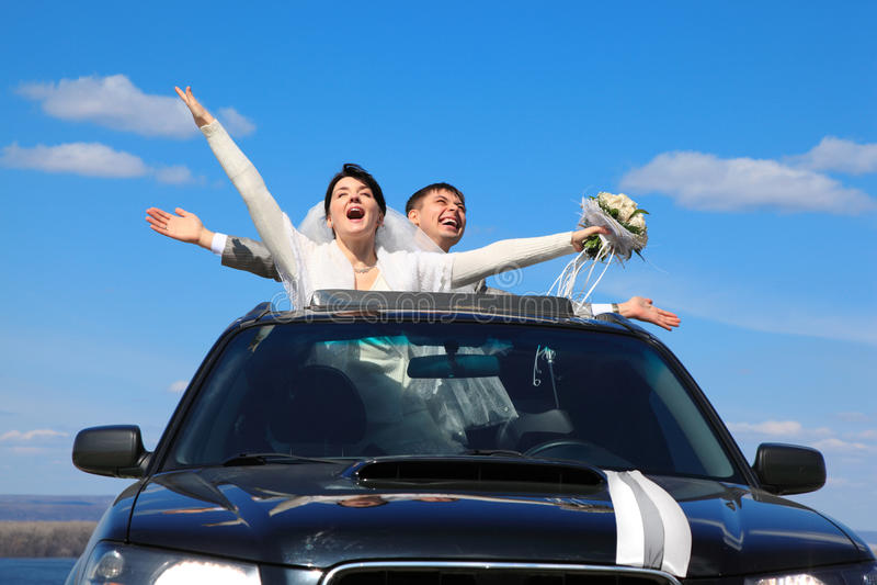 Verlobtes und Braut sind frohe Stellung im Auto lizenzfreie stockfotos