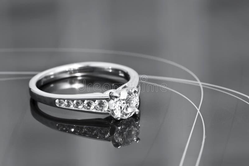 Verlobungsring auf einer reflektierenden Oberfläche stockbilder