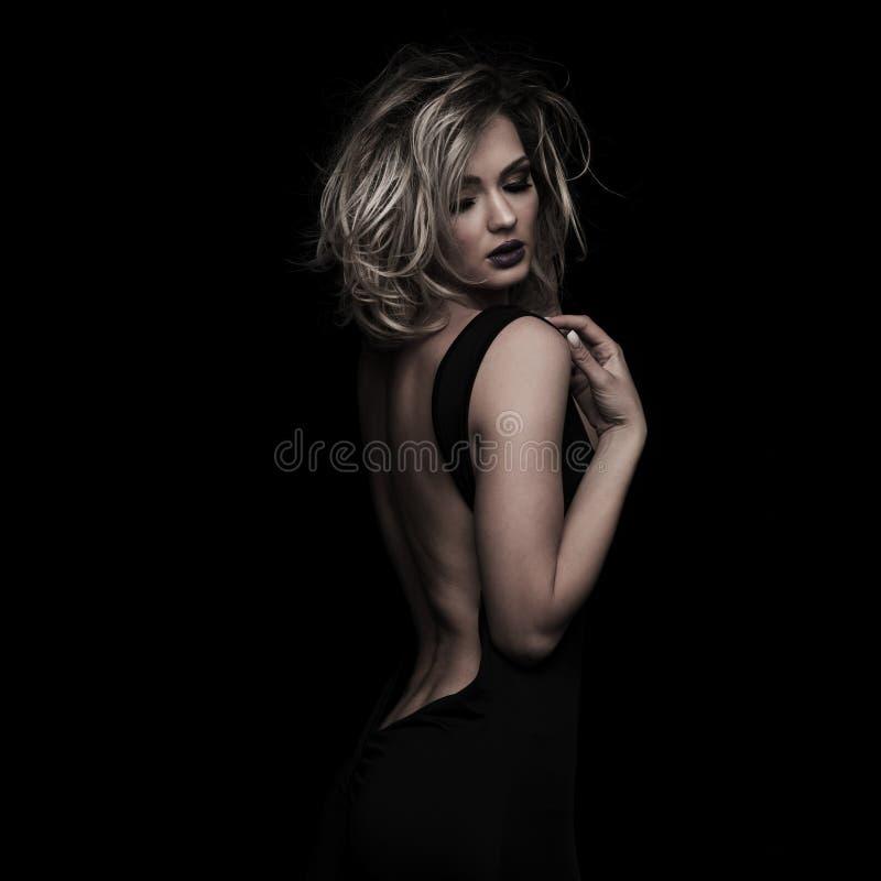 Verlockende elegante Frau mit dem unordentlichen blonden Haar, das unten schaut lizenzfreie stockfotografie