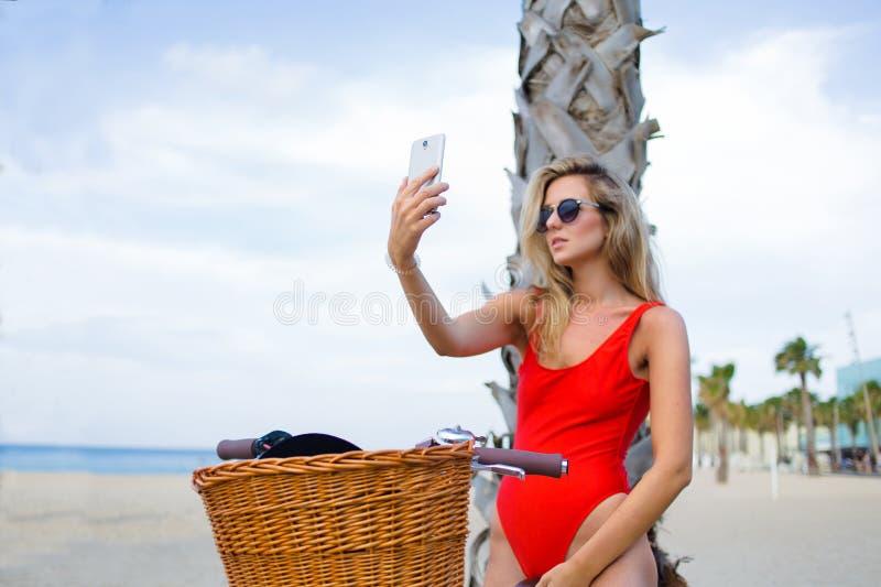 Verlockende Frau in der Badebekleidung, die Selbstporträt mit intelligentem Telefon auf dem Strand nimmt stockbild