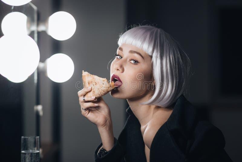 Verlockende Frau in der blonden Perücke Pizza essend und Champagner trinkend stockfotos
