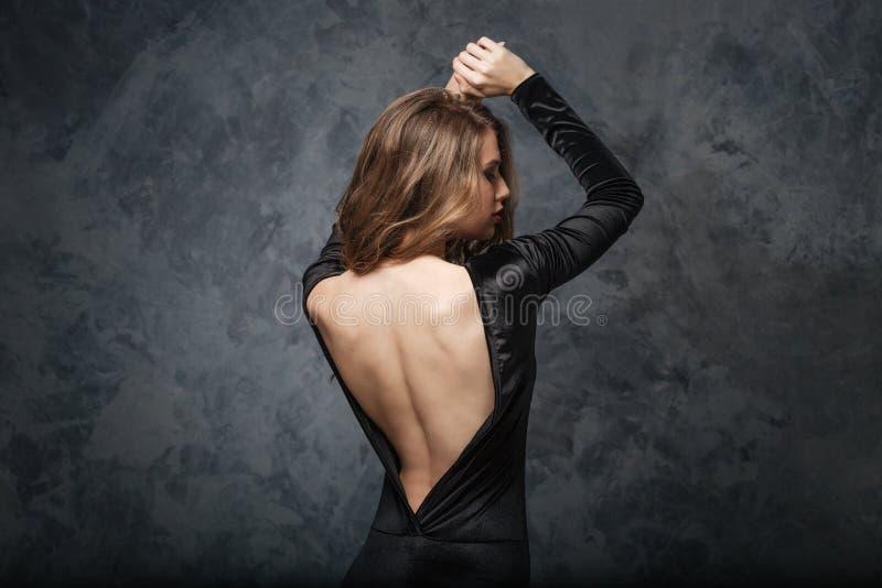 Verlockende junge Frau im Abendkleid mit offenem Rücken stockfotografie