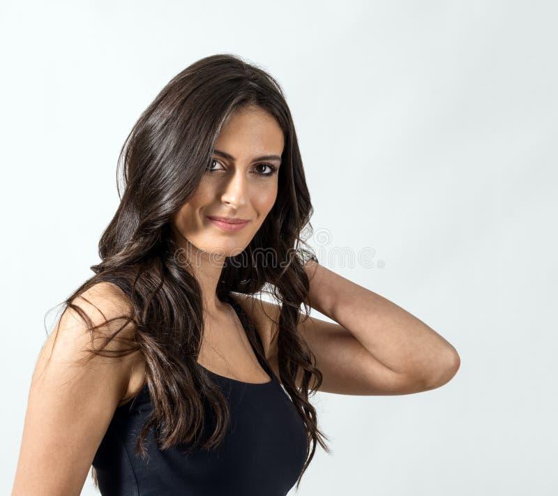 Verlockende Latinoschönheit mit der Hand, die ihr dunkles gesundes gewelltes Haar hält stockfotografie