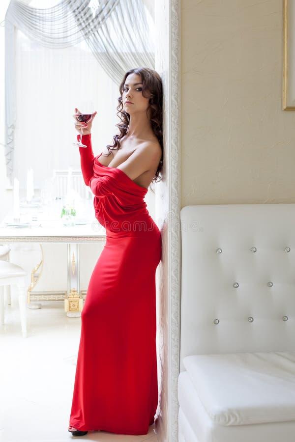 Verlockender Brunette, der im langen roten Kleid aufwirft lizenzfreie stockbilder
