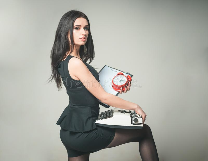Verlockender Sekretär, der Klemmbrett und Schreibmaschine in ihren Händen hält Seitenansicht schöner Brunette, der mit ihrem Bein stockfoto