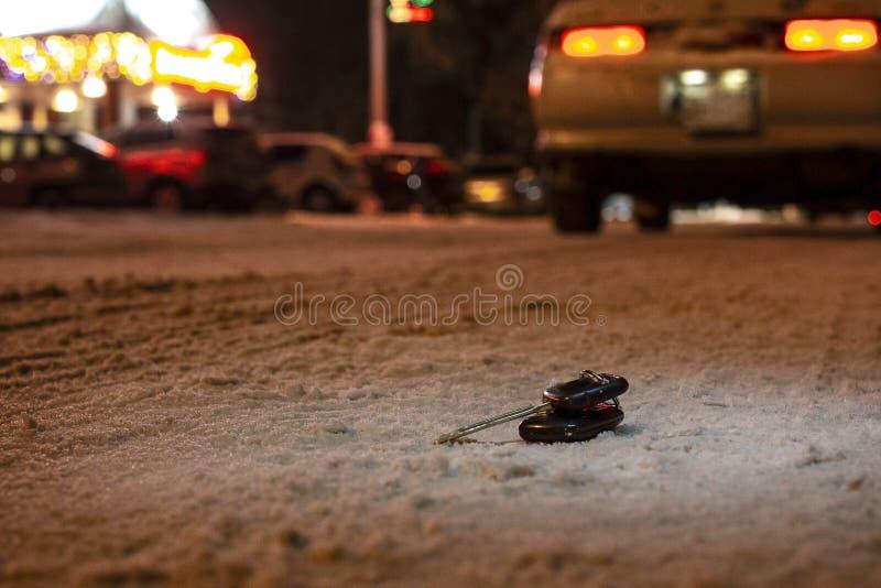 Verloren die autosleutels op de weg met de eerste sneeuw bij nacht wordt gepoederd Op vage achtergrond royalty-vrije stock afbeeldingen