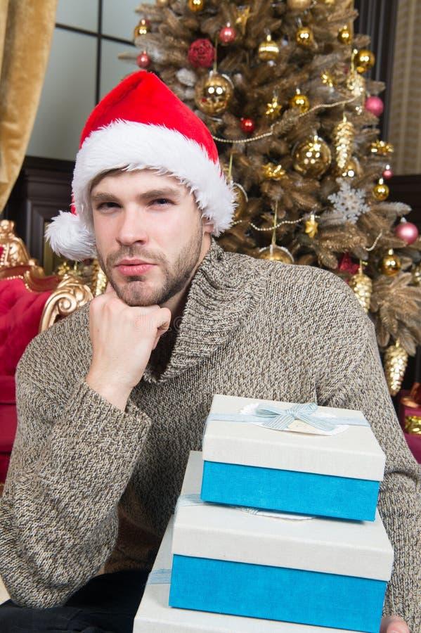 Verloren in Kerstmisgedachten Gelukkige mens met de dozen van de Kerstmisgift De kerel viert thuis Kerstmis mens in de greep van  stock afbeelding