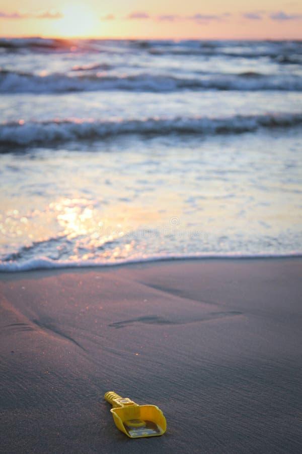 Verloren stuk speelgoed schop op het strand stock foto's