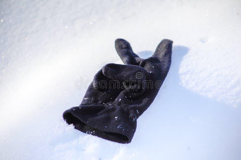 Verloren zwarte handschoen op de sneeuw, close-up stock fotografie