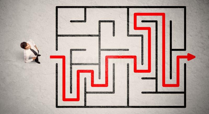 Verlorener Geschäftsmann fand die Weise im Labyrinth mit rotem Pfeil lizenzfreie stockfotos