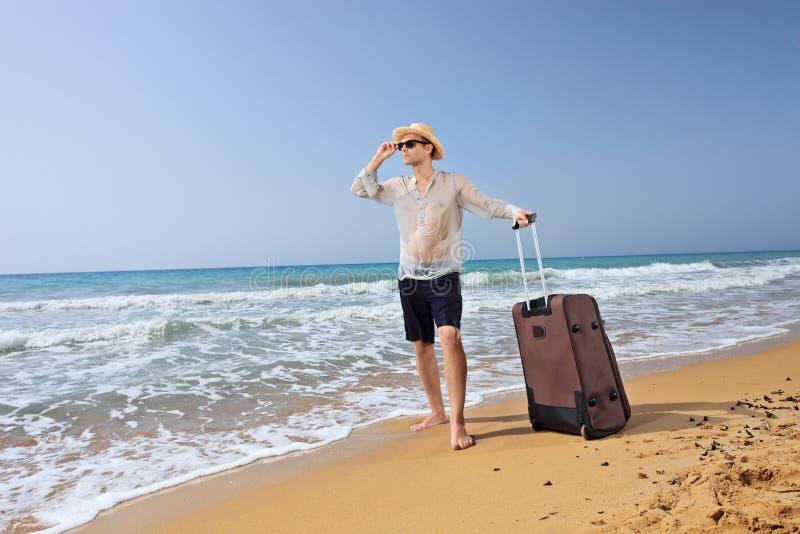 Verlorener junger Tourist mit seinem Gepäck auf einem Strand lizenzfreies stockfoto
