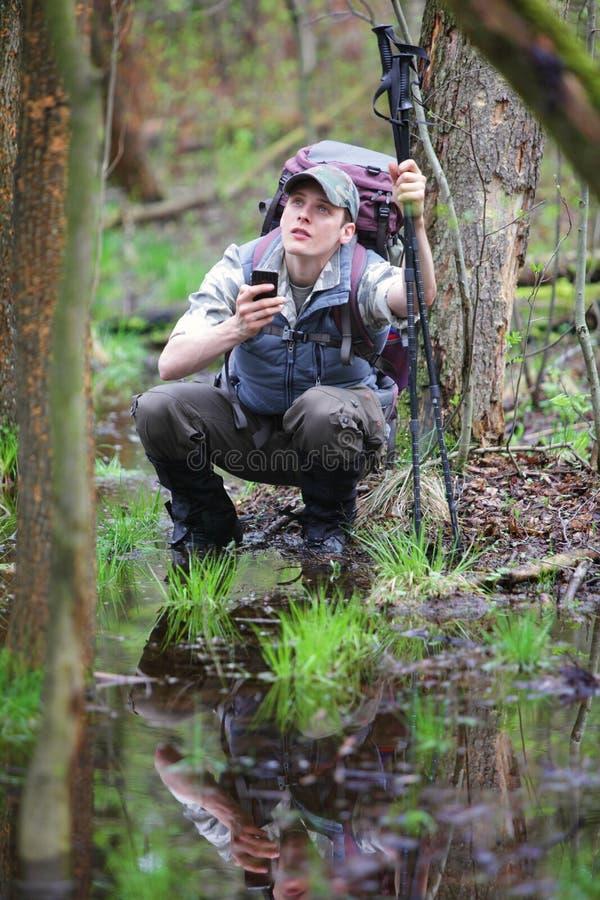 Verlorener Wanderer im Wald mit mobilem Satellitennavigationsgerät stockfotografie