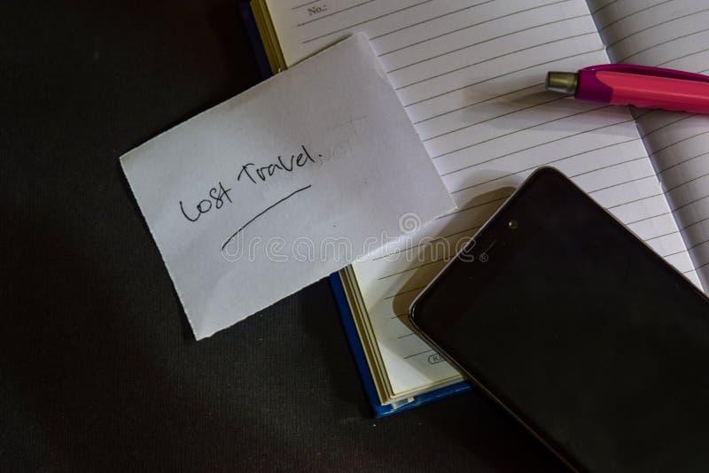 Verlorenes Reisewort geschrieben auf Papier Verlorener Reisetext auf Arbeitsbuch, schwarzes Hintergrundkonzept stockbild