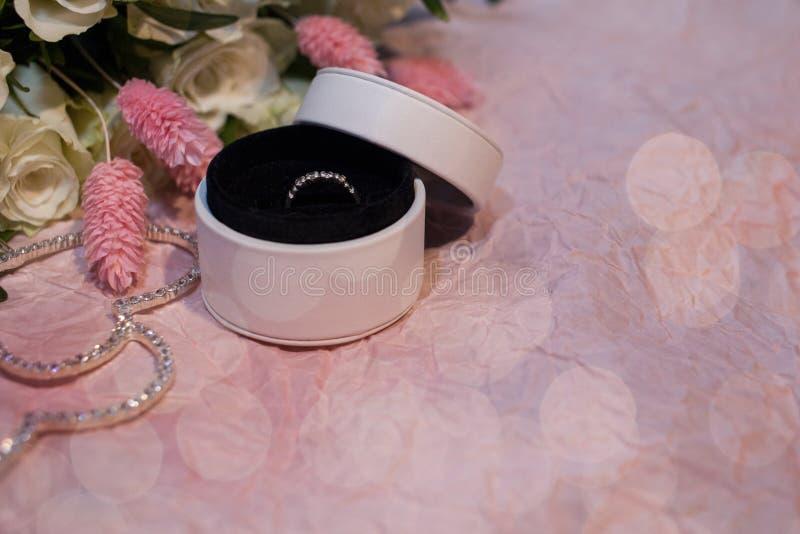 Verlovingsring in een rond wit vakje op een roze document achtergrond met bokeh en met een boeket van witte rozen en a royalty-vrije stock foto