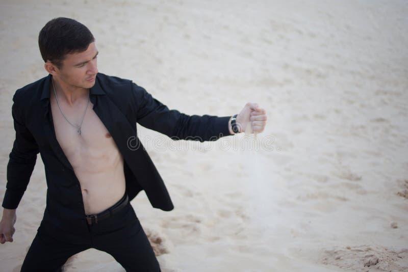 Verlust, Konzept junger Mann, der in der Wüste knit Sand durch Finger lizenzfreie stockfotos