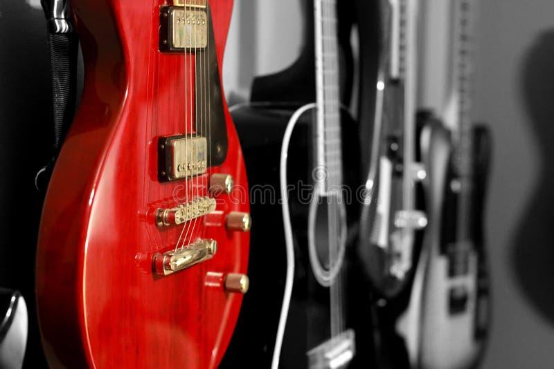 Vermelho contra a parede preto e branco das guitarra imagens de stock royalty free