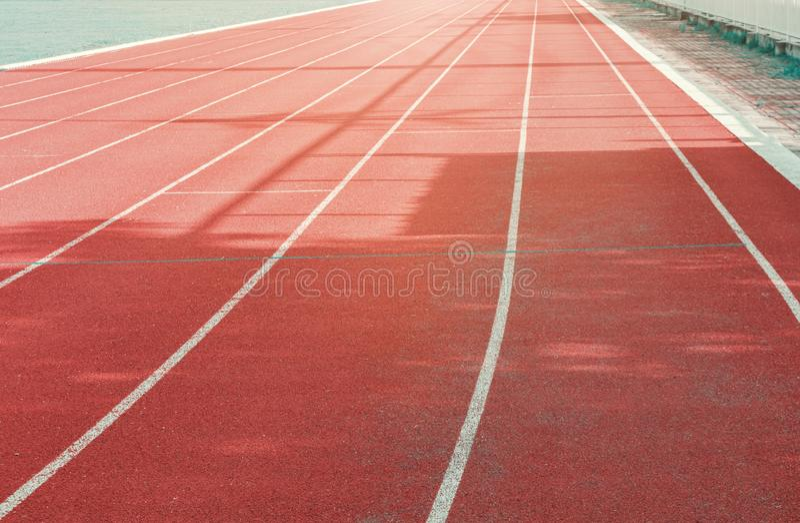 Vermelho da pista de atletismo exterior com linhas brancas e luz solar da manhã imagem de stock