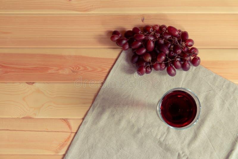 Vermelho de vidro do vinho e de uvas vermelhas no fundo de madeira foto de stock