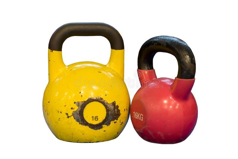 Vermelho e amarelo usados e kettlebells velhos isolados em um fundo branco Equipamento do exercício imagens de stock royalty free
