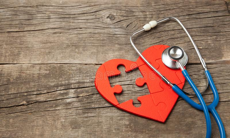 Vermelho e estetoscópio do enigma do coração no fundo de madeira Diagnóstico do conceito e tratamento da doença cardíaca, seguro  foto de stock
