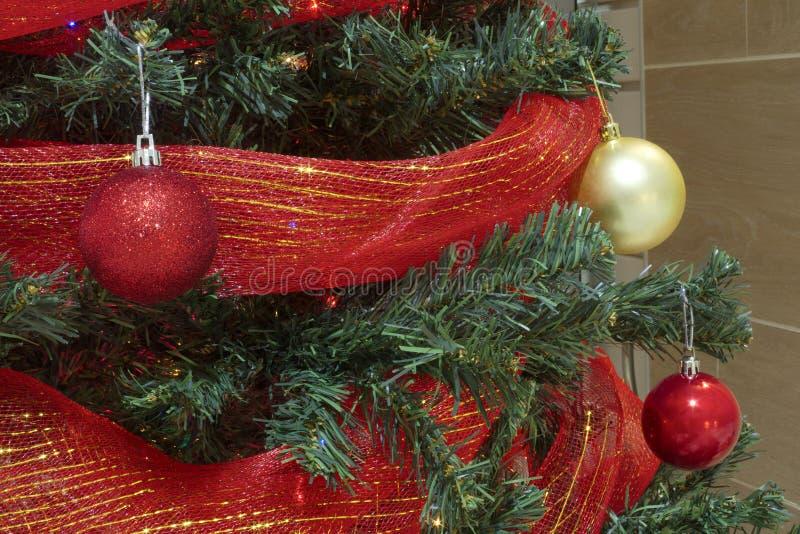 Download Vermelho E Quinquilharias Do Natal Do Ouro Com Fita Em Uma árvore Foto de Stock - Imagem de fundo, decoração: 80102498