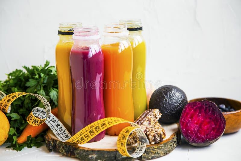 Vermelho, laranja, sucos verdes e amarelos, garrafas frescas dos batidos com verdes e frutis, fita mesuring e barras do muesli, s fotografia de stock