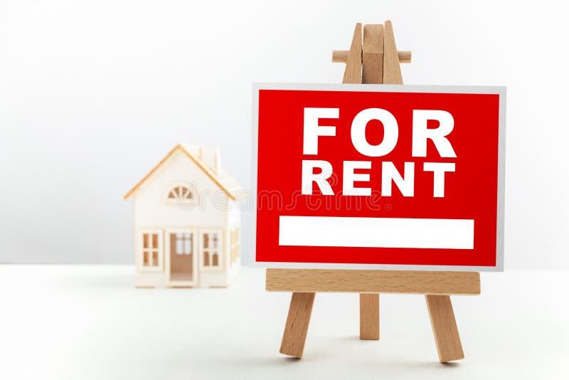 Vermelho para o sinal de Real Estate do aluguel na frente do modelo da casa pequena foto de stock royalty free