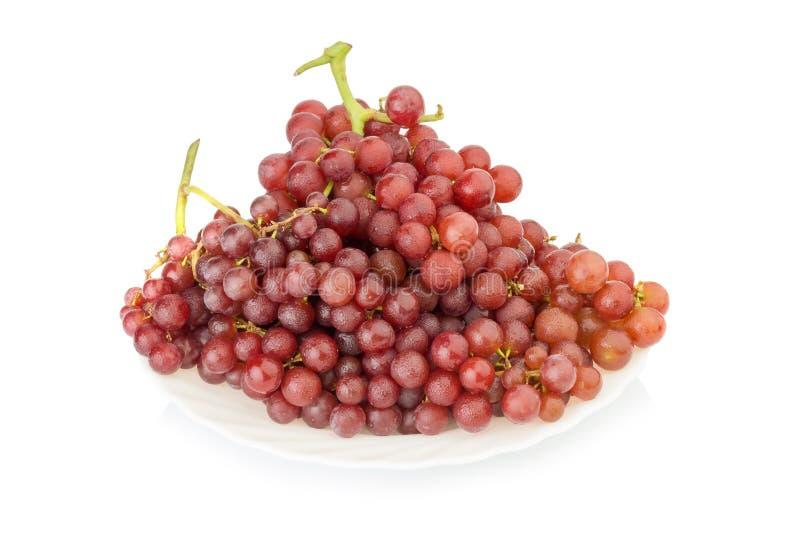 vermelho sem sementes das uvas no prato isolado no fundo branco imagens de stock royalty free