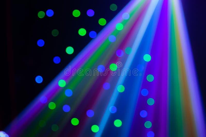 Vermelho, verde, roxo, branco, rosa, lasers azuis que cortam através do fumo da máquina do fumo imagem de stock royalty free