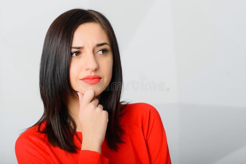 Vermelho vestindo preocupado novo pensativo moreno da mulher imagens de stock