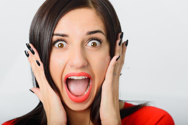 Vermelho vestindo shoked morena da jovem mulher alegre fotografia de stock