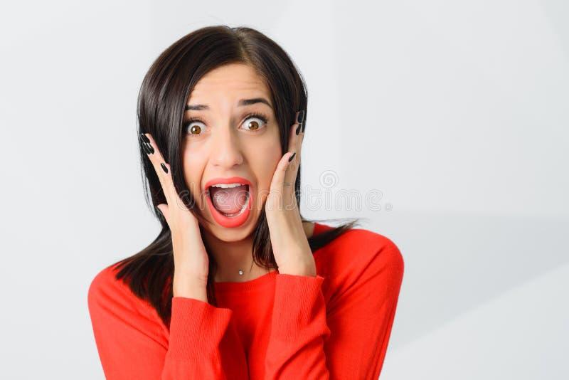 Vermelho vestindo shoked morena da jovem mulher assustado fotos de stock royalty free