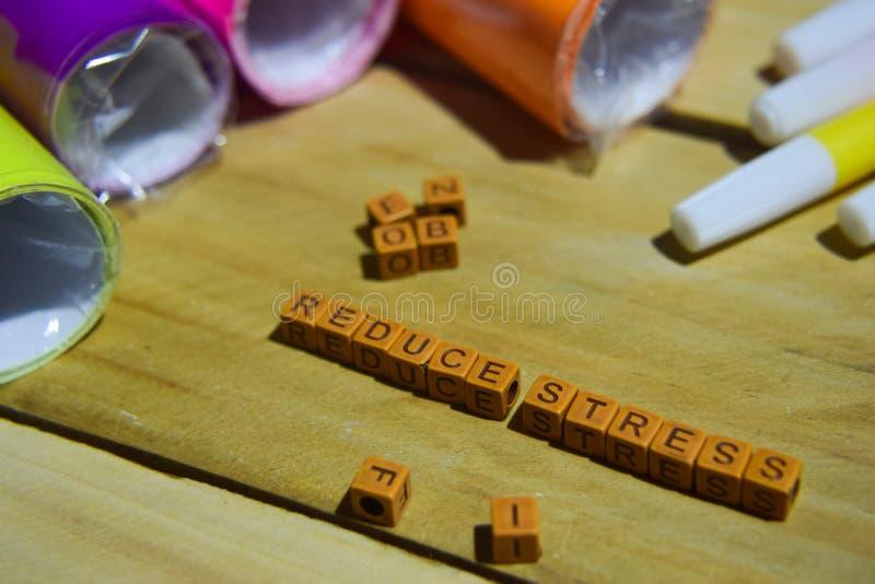 Verminder Spanning op houten kubussen met kleurrijke document en pen, Concepteninspiratie op houten achtergrond stock afbeeldingen