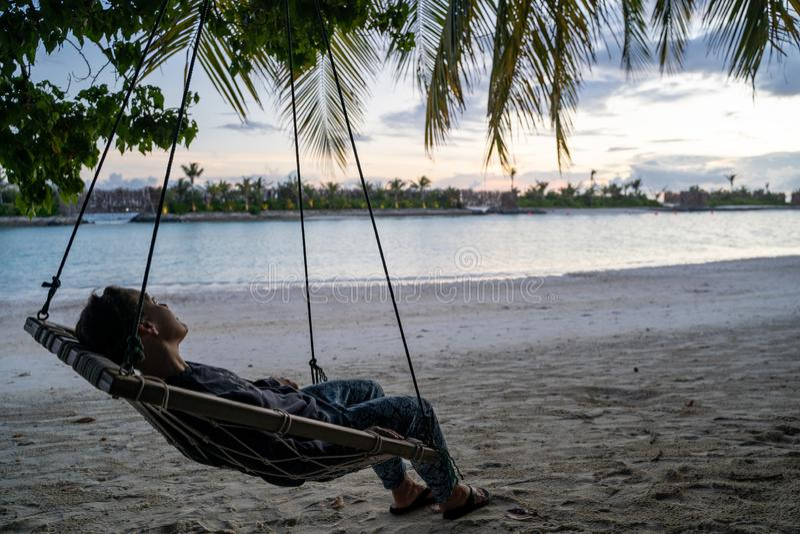 Verminderde vrouw zit in een hammock die de Indische Oceaan in de Malediven overziet op zonsondergang royalty-vrije stock afbeeldingen