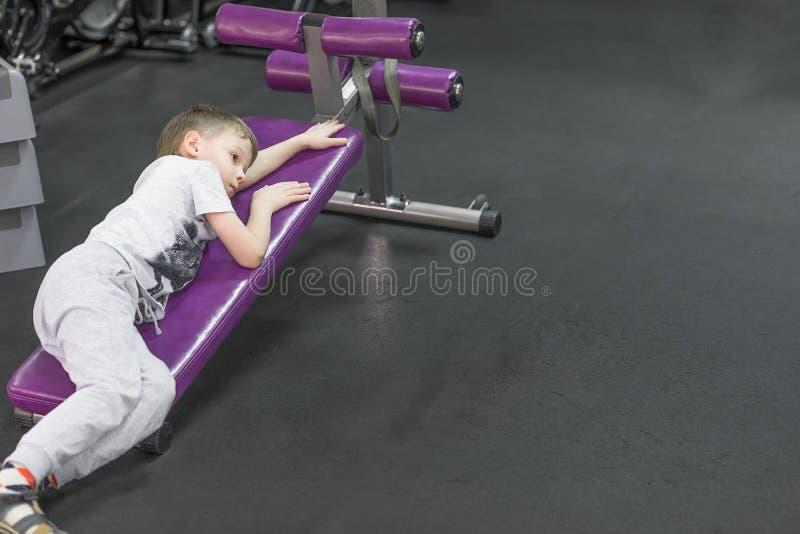 Vermoeid Bored verstoord weinig jongen in gymnastiek royalty-vrije stock afbeeldingen