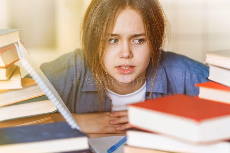 Vermoeid die bored tienermeisje door moeilijke te leren wordt verstoord stock foto