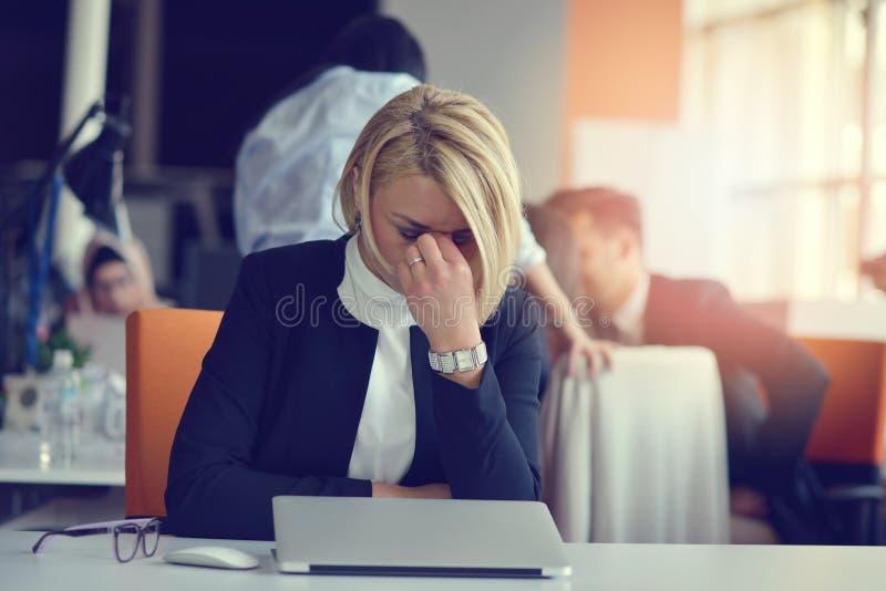 Vermoeid en beklemtoond gevoel De gefrustreerde volwassen vrouw die ogen houden sloot van moeheid terwijl het zitten in bureau royalty-vrije stock afbeeldingen