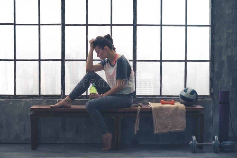 Vermoeid, geschikt vrouwen rustend hoofd op handzitting in zoldergymnastiek stock foto