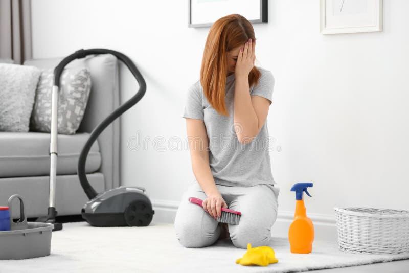Vermoeid huisvrouwen schoonmakend tapijt stock foto